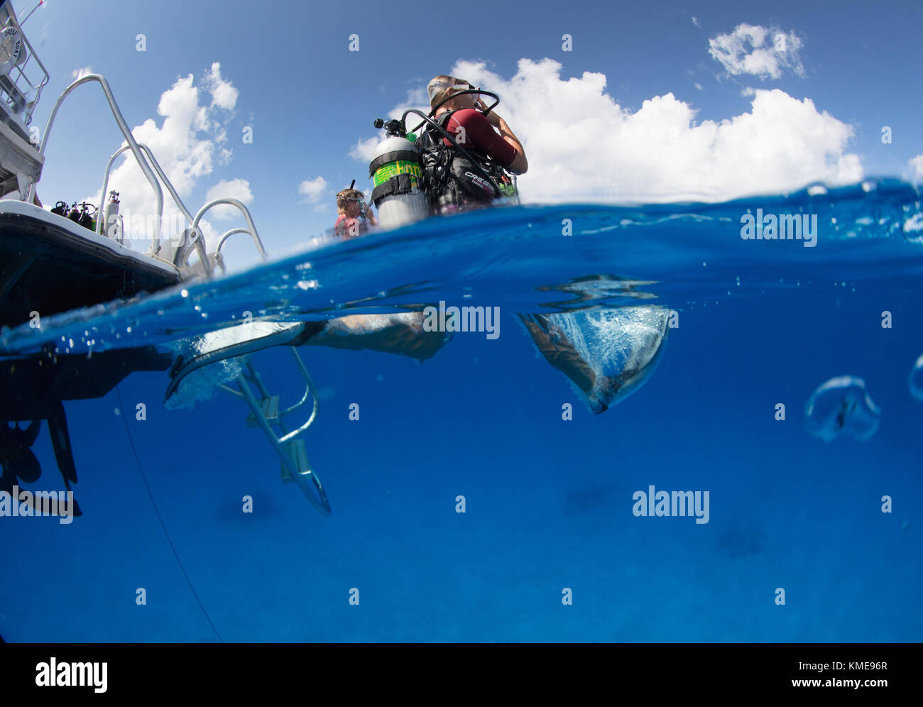 Scuba divers enter water doing giant stride. Stock Photo