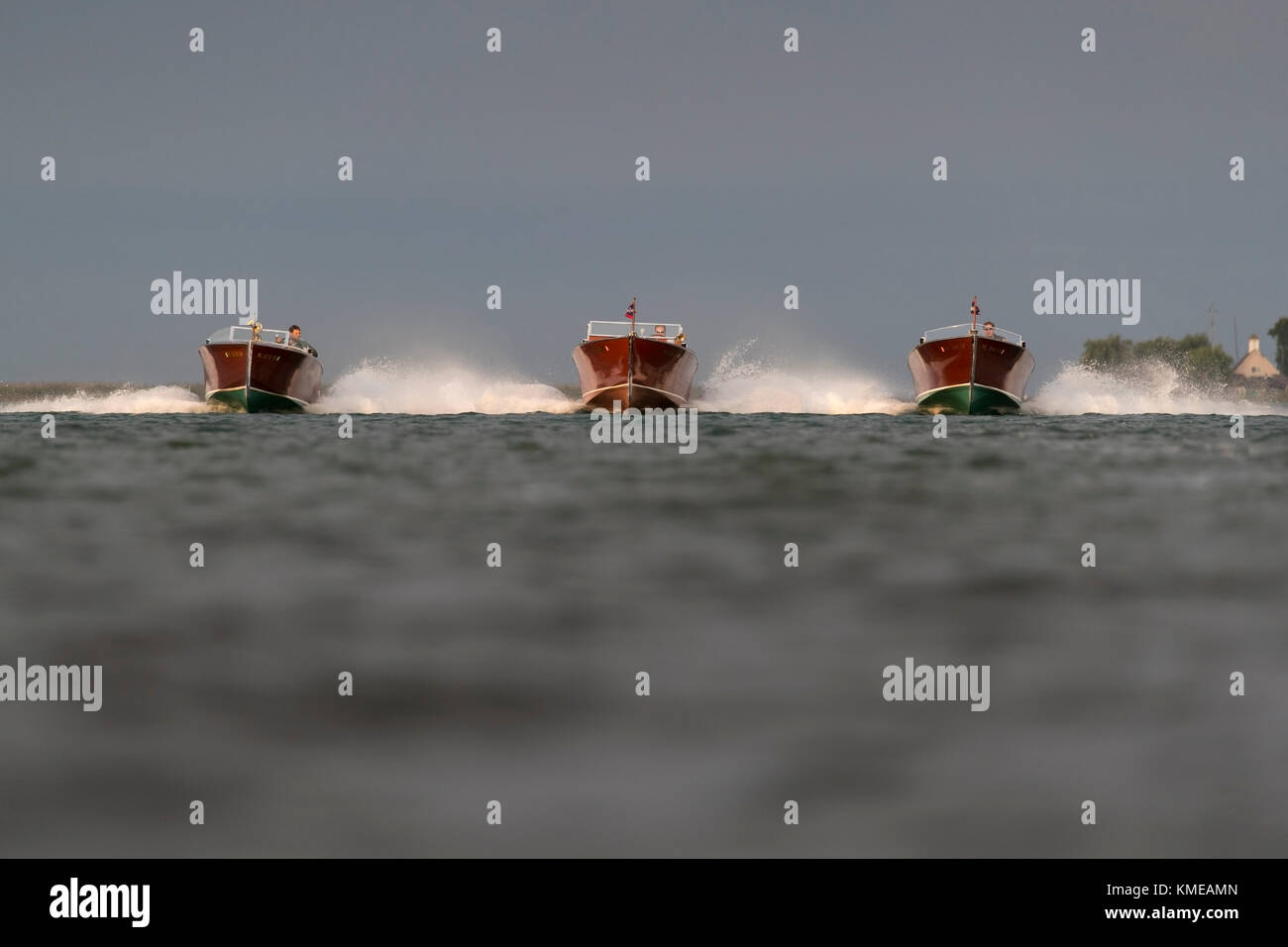 Three wooden speedboats approaching in formation. - Stock Image