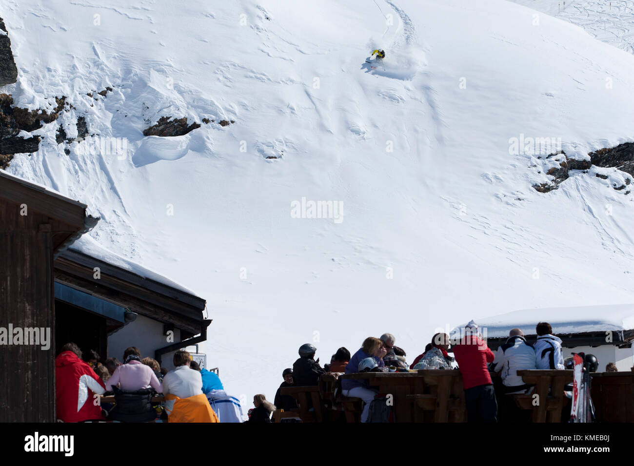 Man skiing as onlookers watching from lodge,Corvatsch,Switzerland - Stock Image