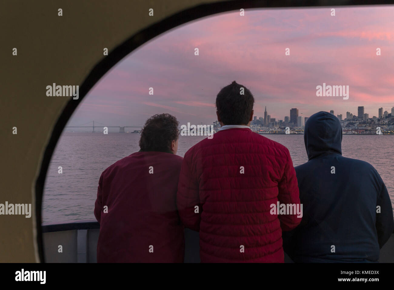 rear view of three passengers on ferry from Sausalito to San Francisco looking at view of city,California,USA - Stock Image