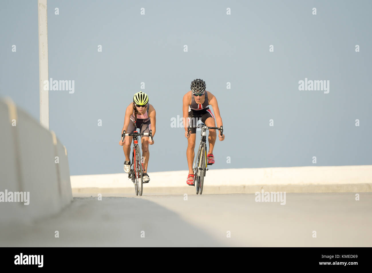 Two cyclists riding bicycles against clear sky during triathlon race,Veracruz,Mexico - Stock Image