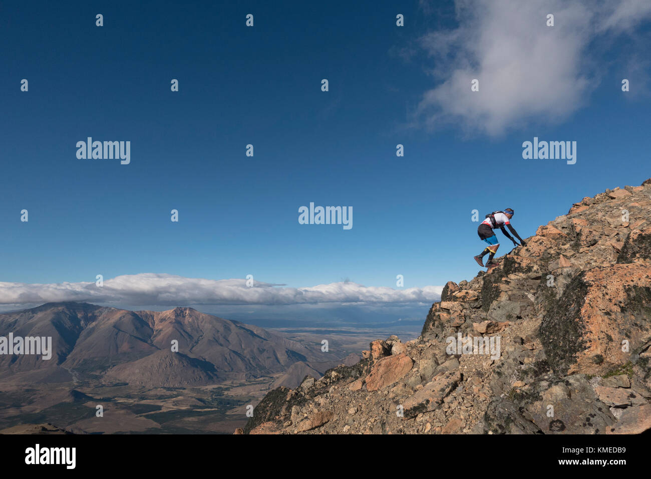 Man climbing rocky mountain against clouds and sky, Esquel, Chubut, Argentina - Stock Image