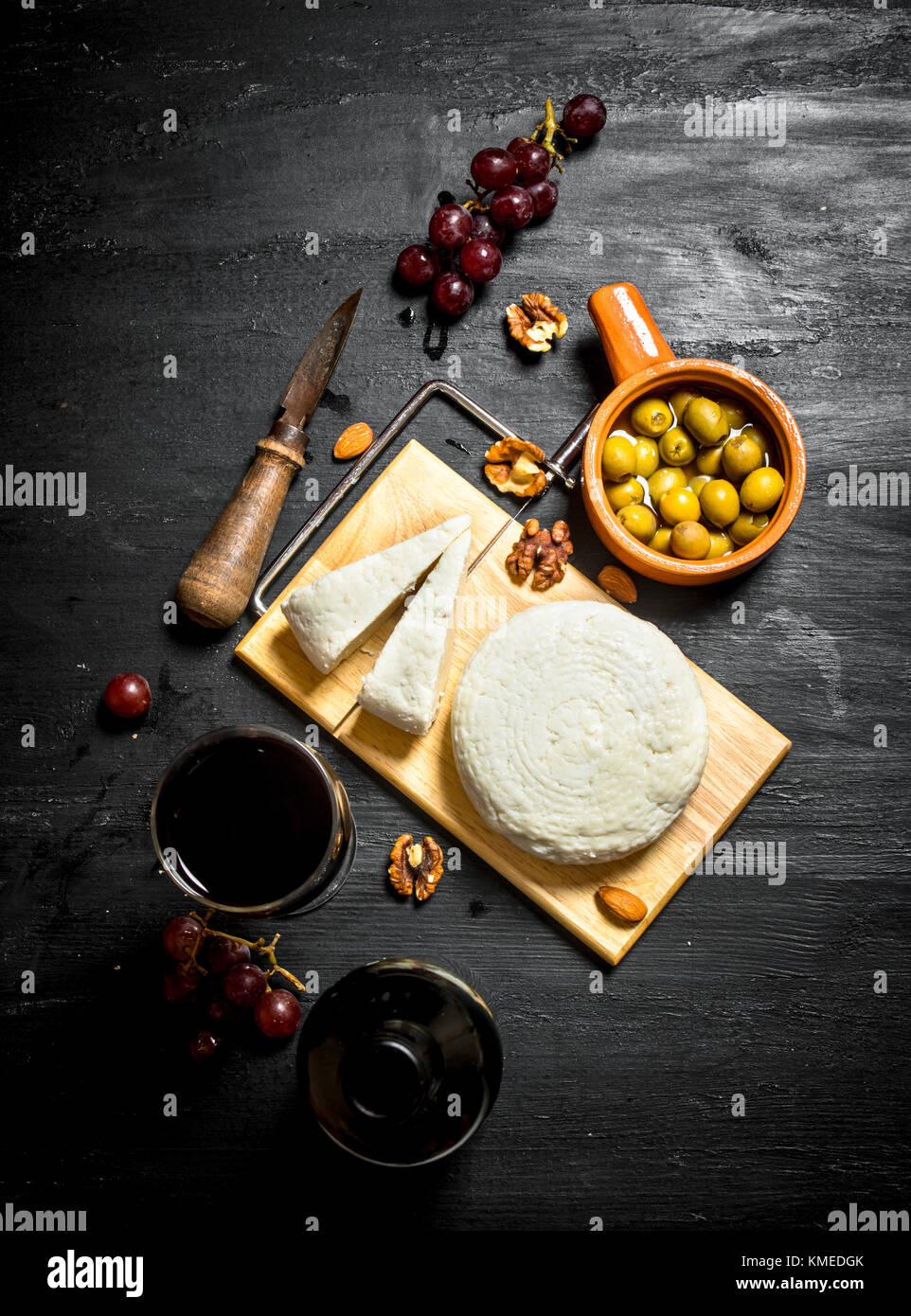 Sheep cheese with red wine , nuts and olives . - Stock Image