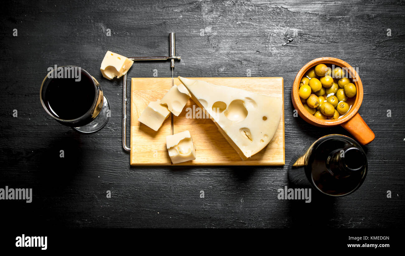 Bottle of red wine with a slice of cheese and on the Board. On a black wooden background. - Stock Image