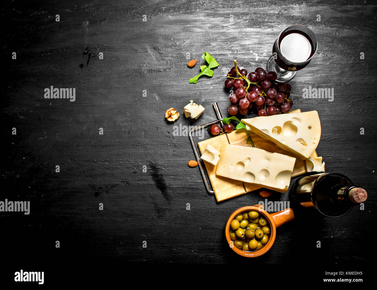 Red wine with a fragrant cheese , olives and almonds. - Stock Image
