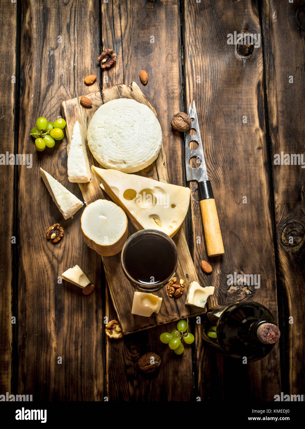 Red wine with chunks of cheese and nuts. On a wooden table. - Stock Image