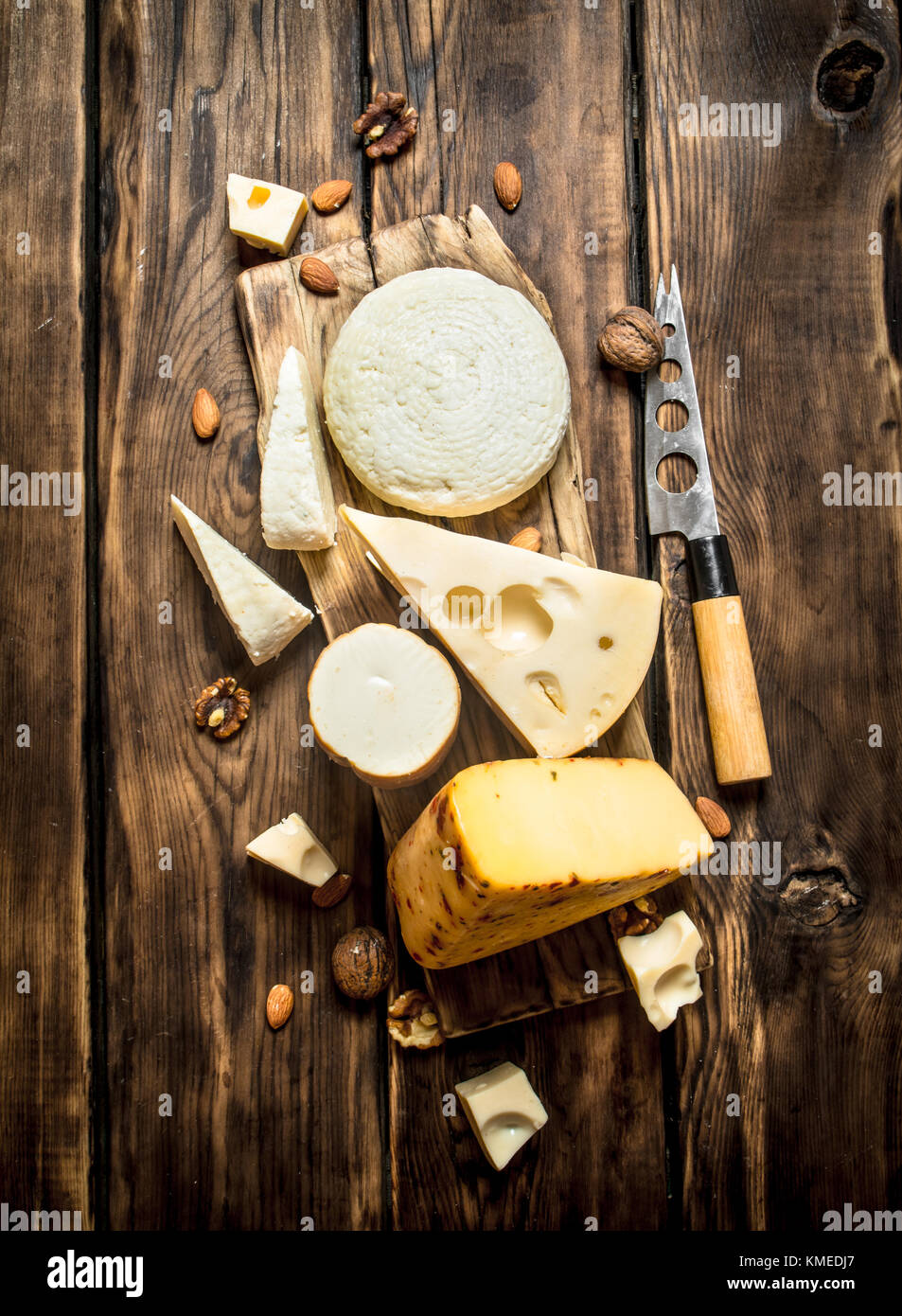 Pieces of cheese with nuts on a Board with a knife. On a wooden table. - Stock Image