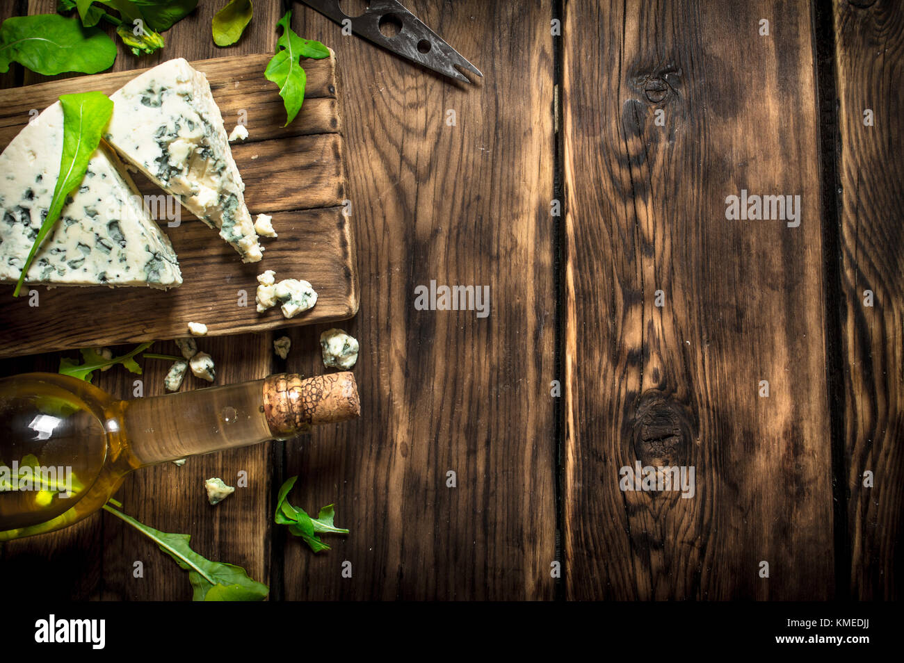 Bottle with white wine and blue cheese on a cutting Board. - Stock Image