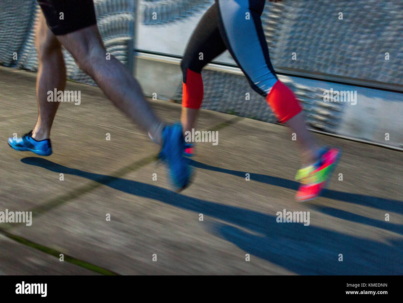 Two runner's feet running quickly on the sidewalk in Seattle, WA. - Stock Image