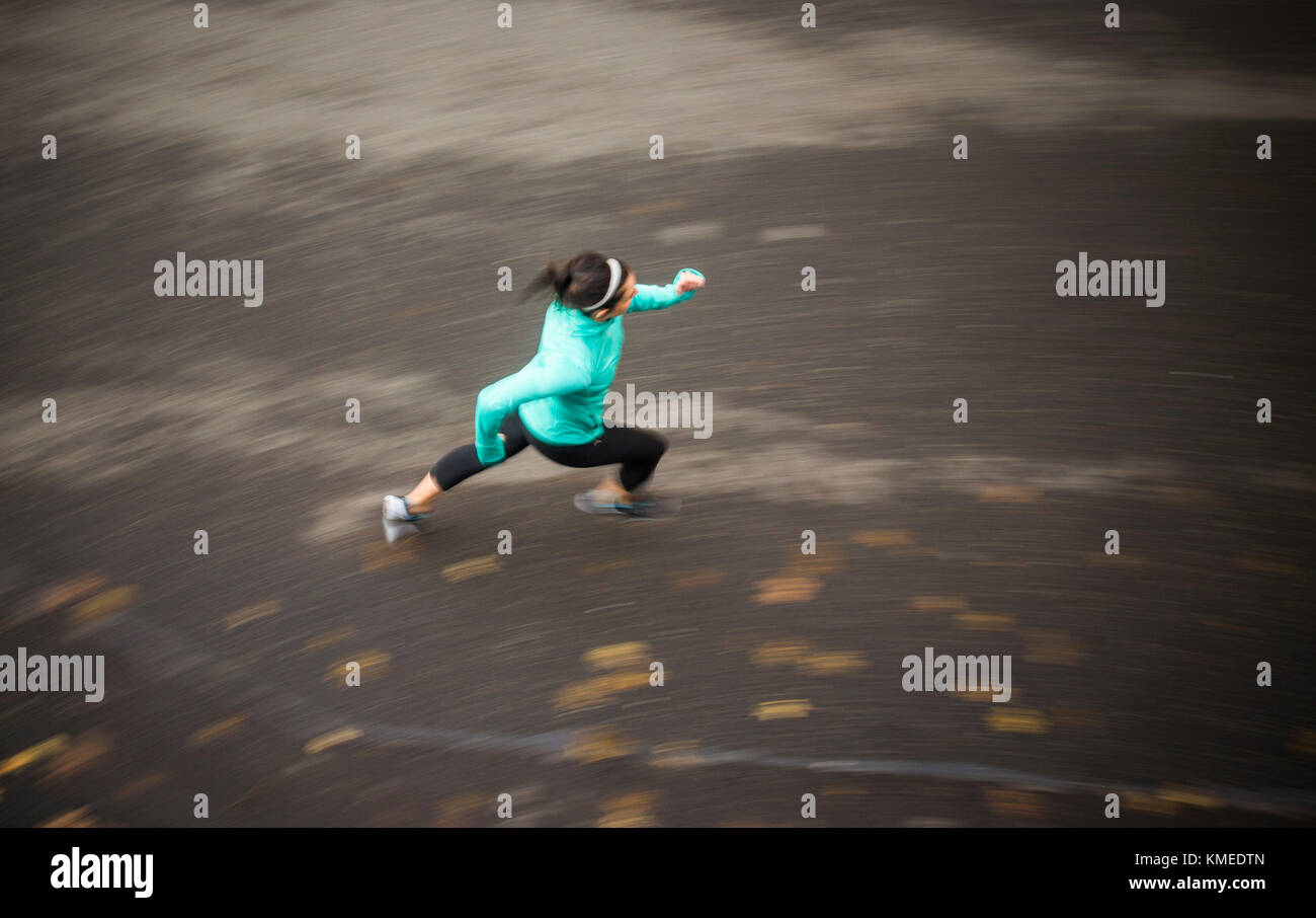 A blurry image of a young woman running on a road shot from above. - Stock Image