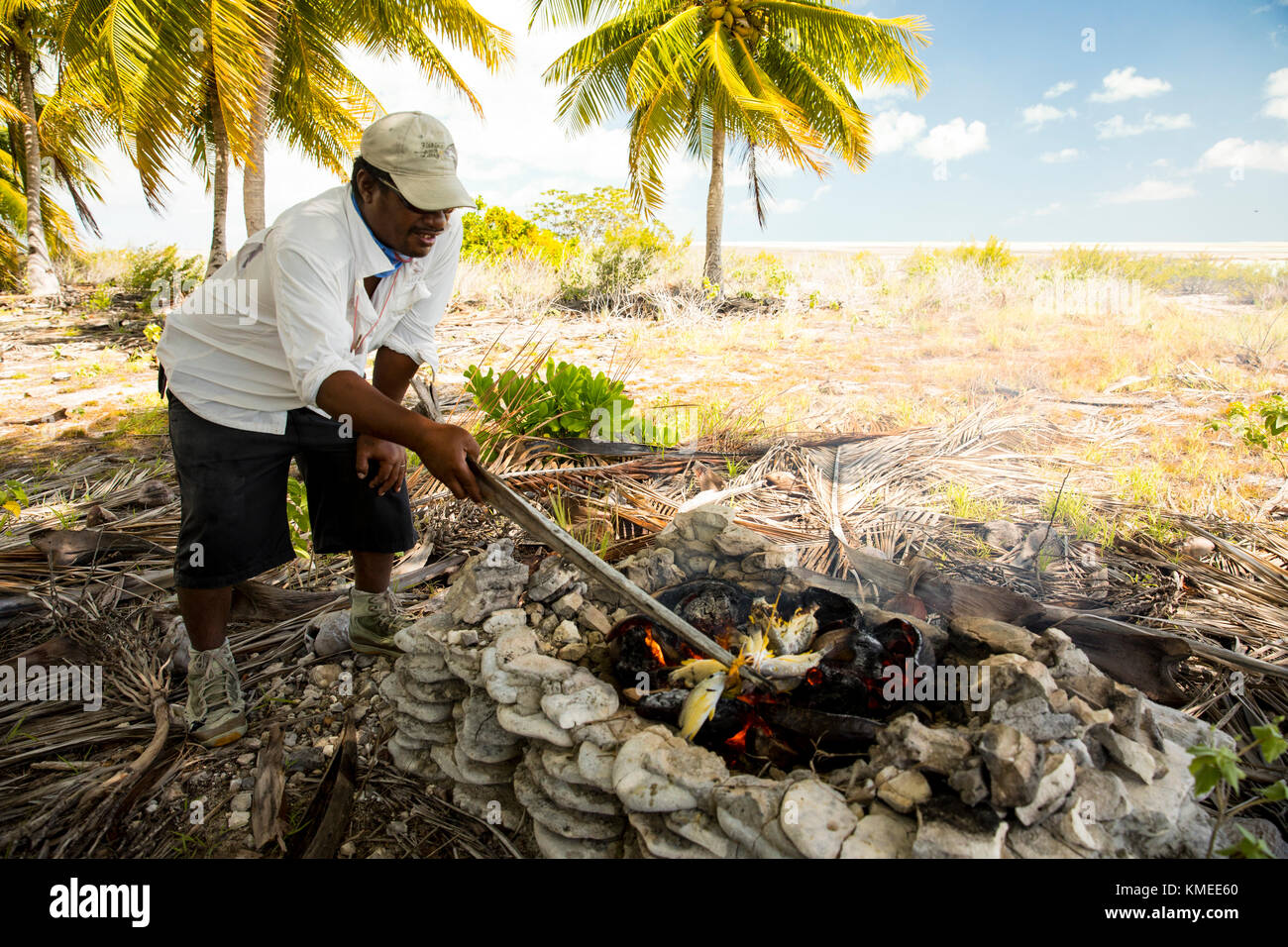 Cooking lunch on coconut frond fire, Kiribati - Stock Image