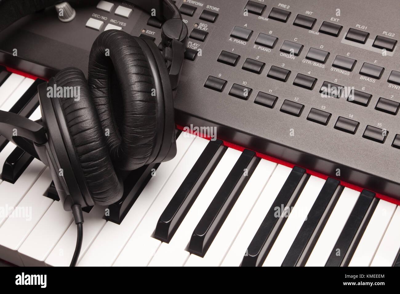 Listening Headphones Laying on Electronic Synthesizer Keyboard. - Stock Image