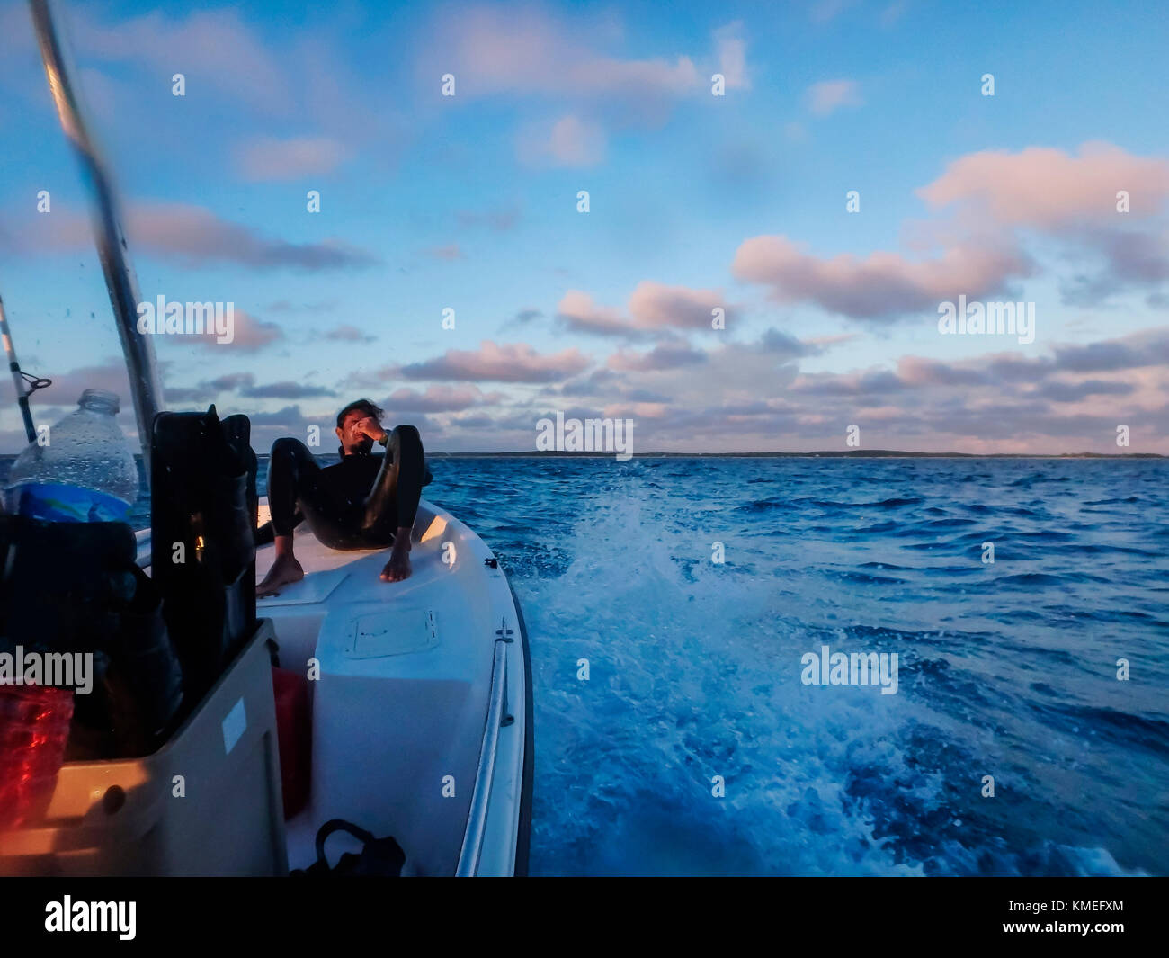 Diver resting on bow of boat while returning from spearfishing and freediving trip, Clarence Town, Long Island, Stock Photo