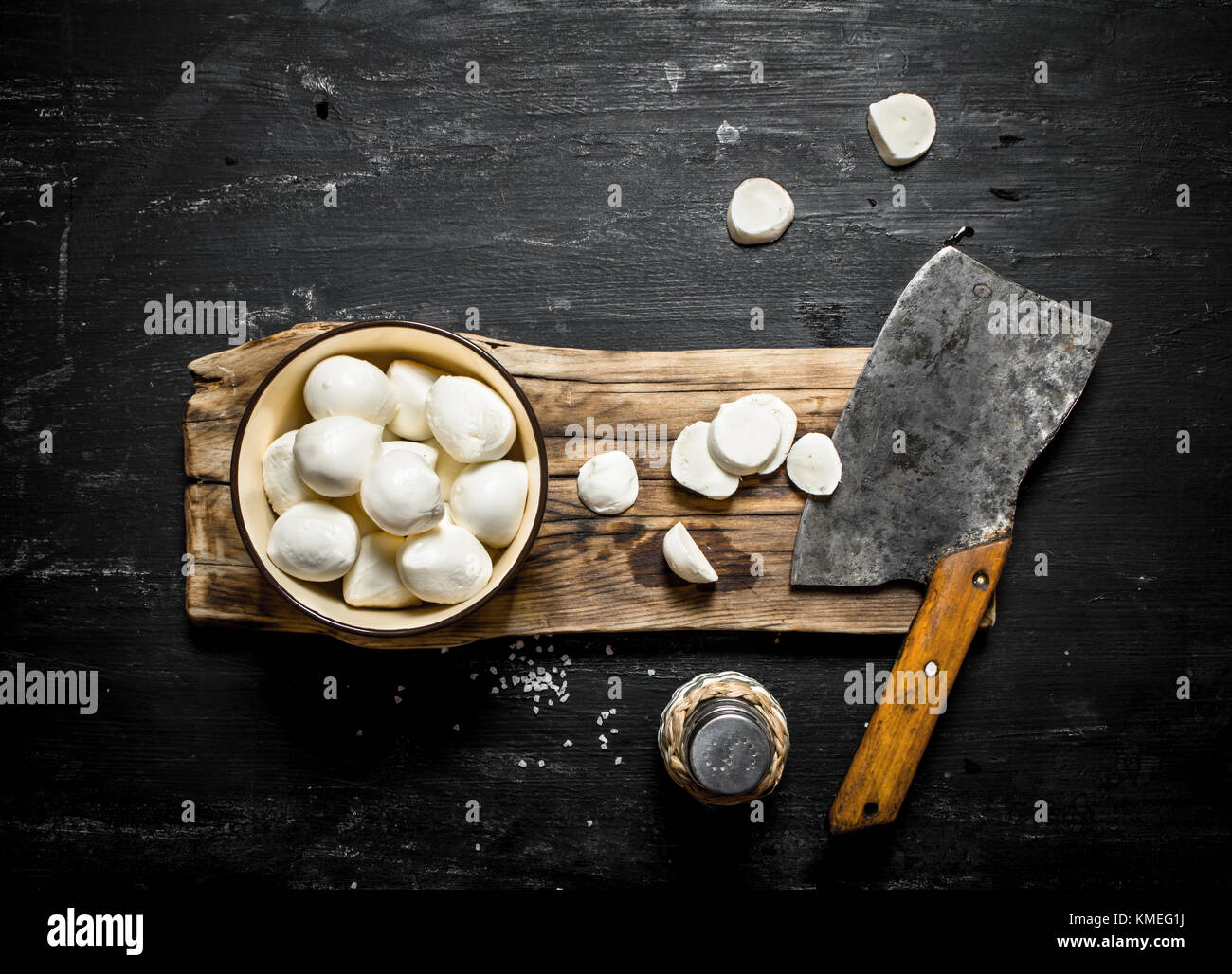 Fresh mozzarella with a hatchet for cutting. On a black wooden background. - Stock Image