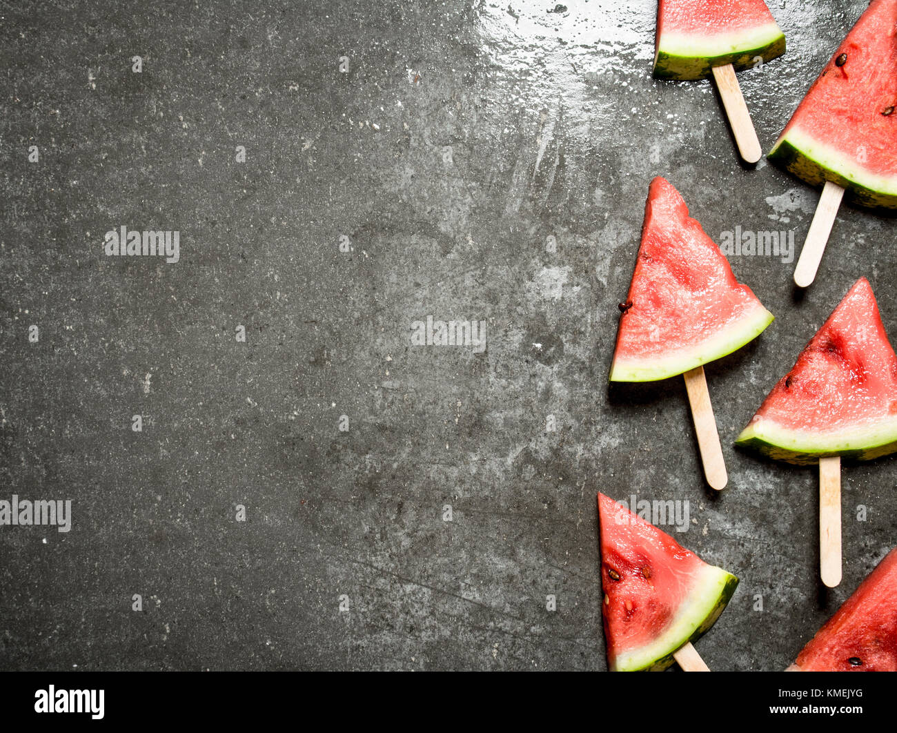 Slices of watermelon on wooden sticks. On the stone table. - Stock Image