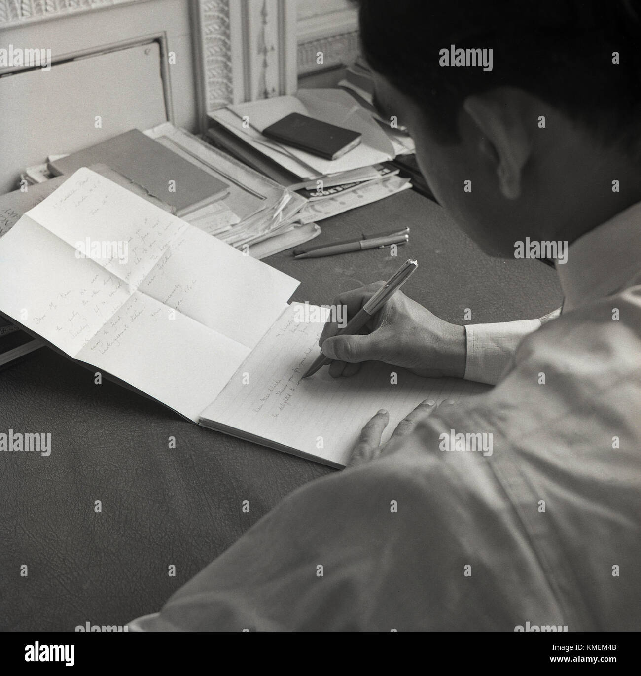 1950s, historical, written correspondence, a man writing a thank you letter with a pen in reply to an invitation - Stock Image