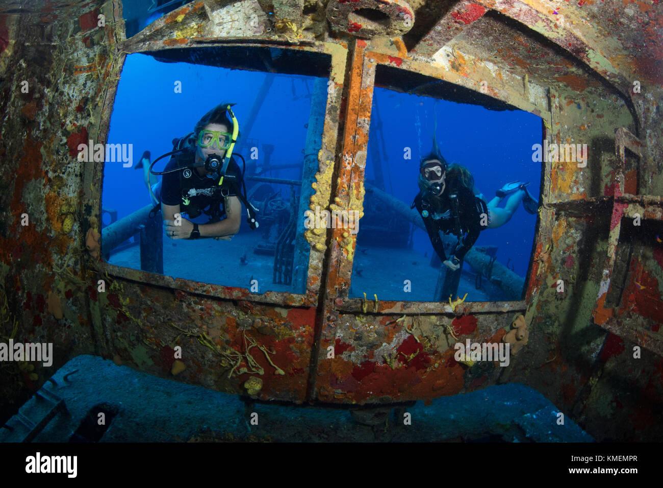 Divers peer through windows on bridge of USS Kittiwake Stock Photo