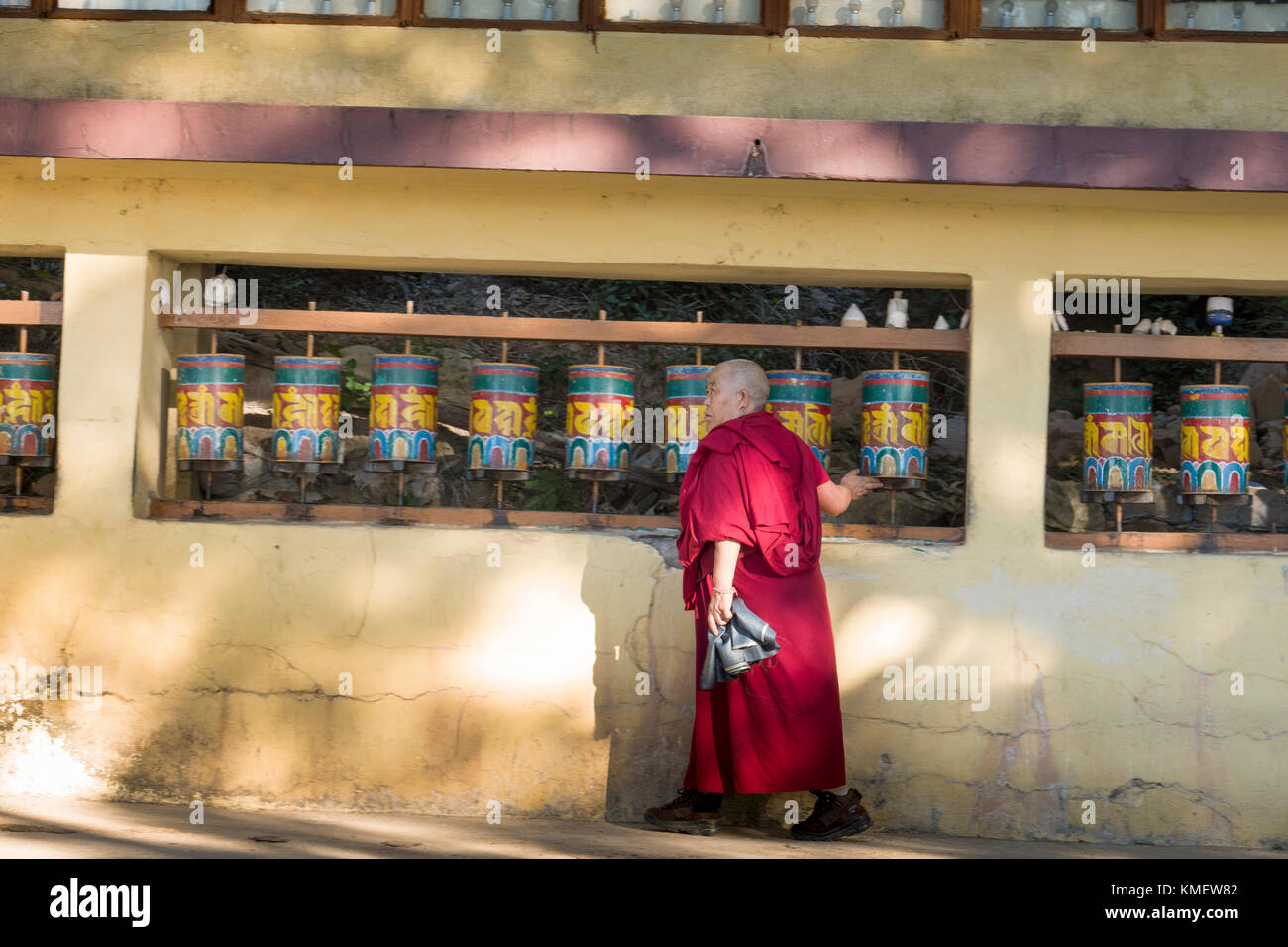 Tibetan monk spins prayer wheels at monastery in Mcleod Ganj, India - Stock Image