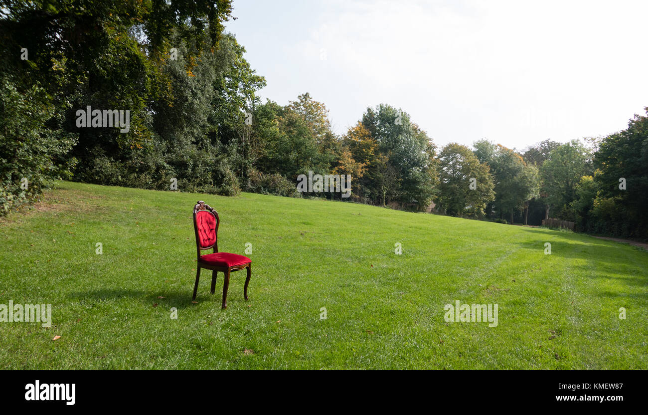A red chair on green grass - Stock Image