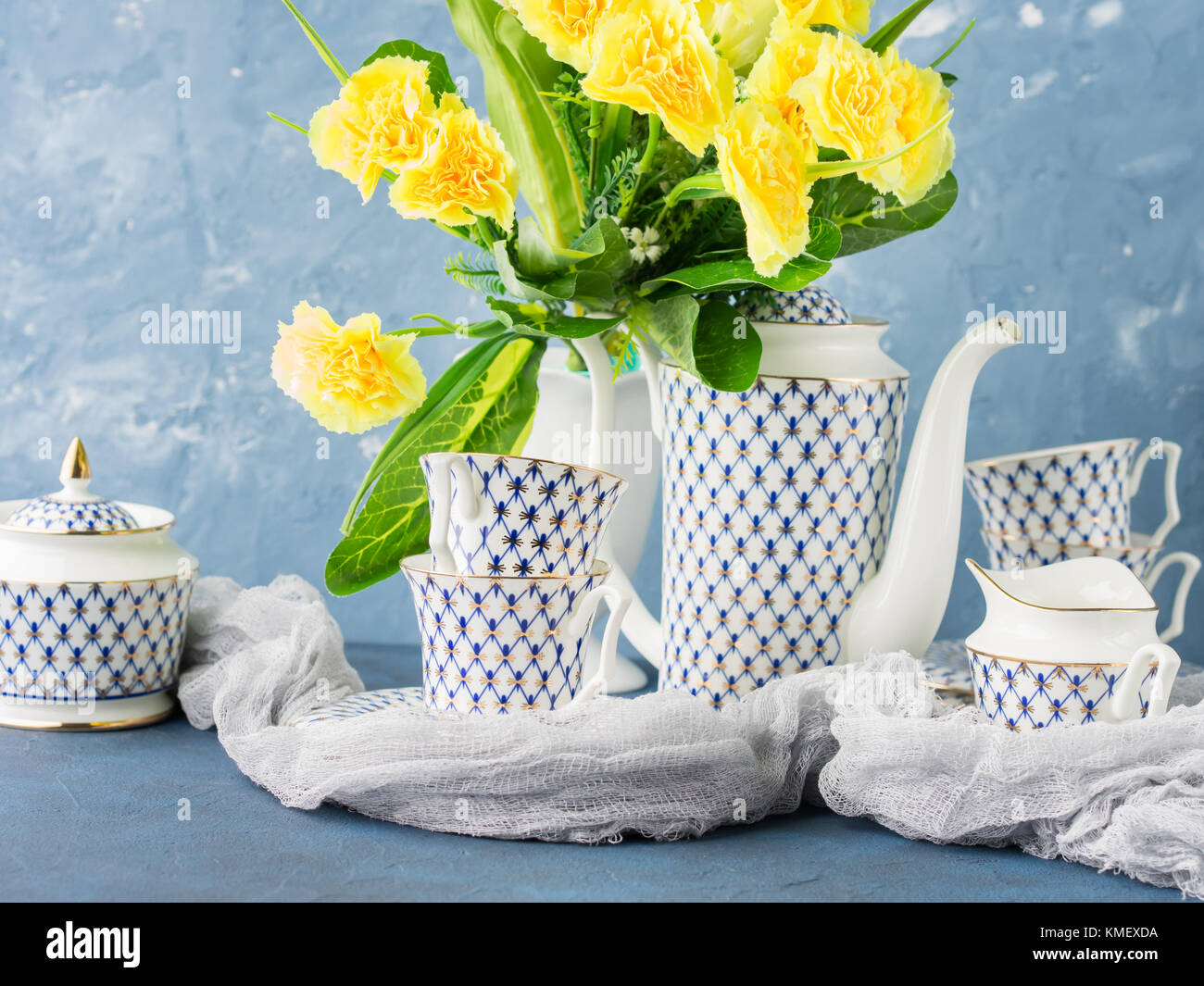 Coffee tea party china set and Easter pastel color yellow flowers on blue. Festive holiday