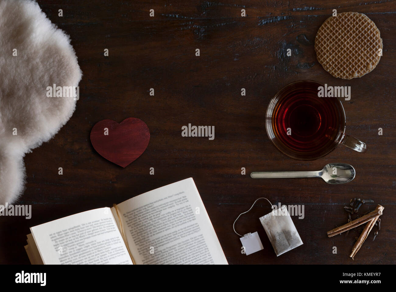 beautiful cozily flat lay of cup of tea, book, sheepskin, cookie and spices on rustic wooden ground - Stock Image