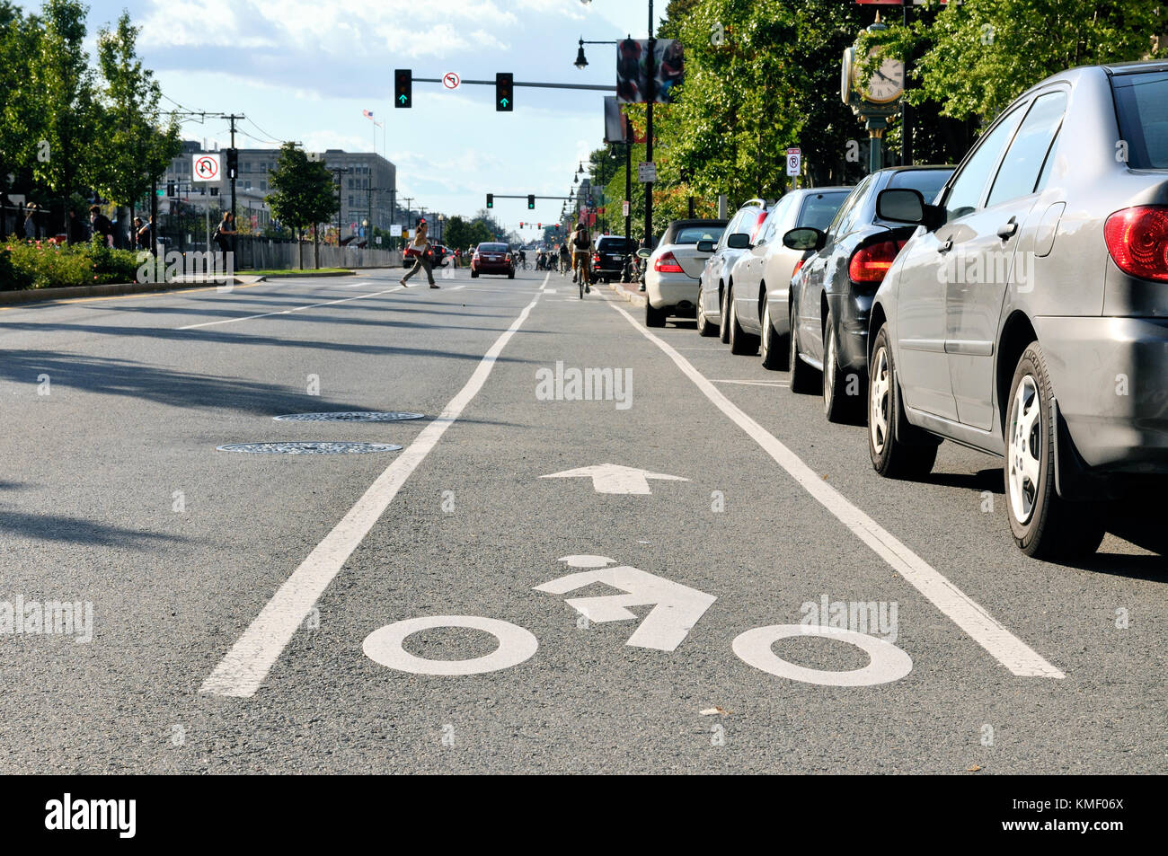 Bike lane in city street. Cyclist symbol painted on pavement, bikers ...