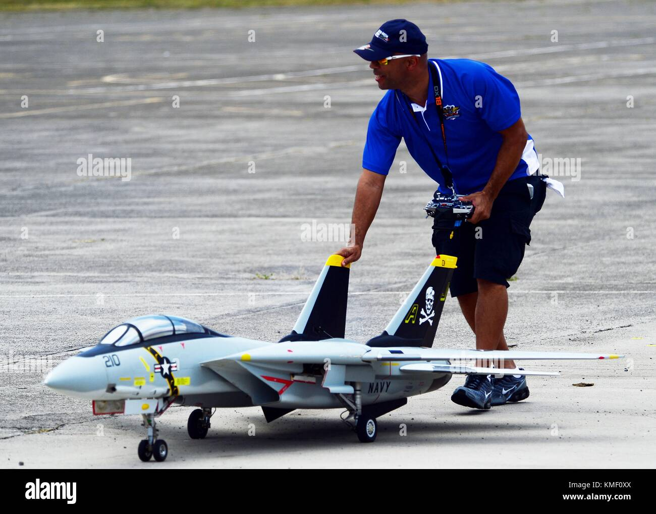 A participant walks a model F-14 Tomcat Jolly Rancher fighter aircraft to the staging area during the Biggest Little - Stock Image