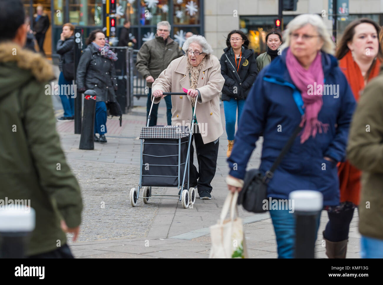 Elderly woman walking in a busy city at shops with a shopping trolley as part of a wheeled walker, in the UK. - Stock Image