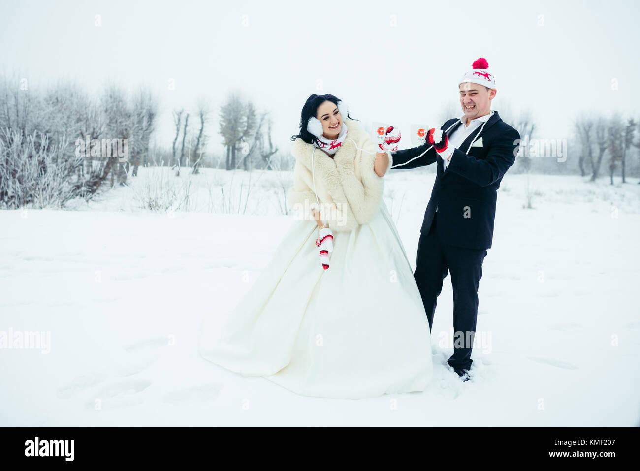 Joyful newlyweds in funny colourful hats and gloves are holding cups while spending great time on the snowy meadow. - Stock Image