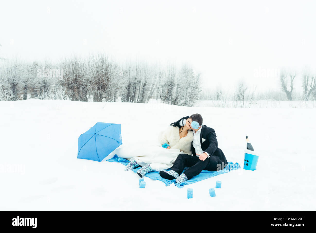 Winter picnic in blue colours of happy kissing newlyweds sitting on the plaid on the snowy meadow. - Stock Image