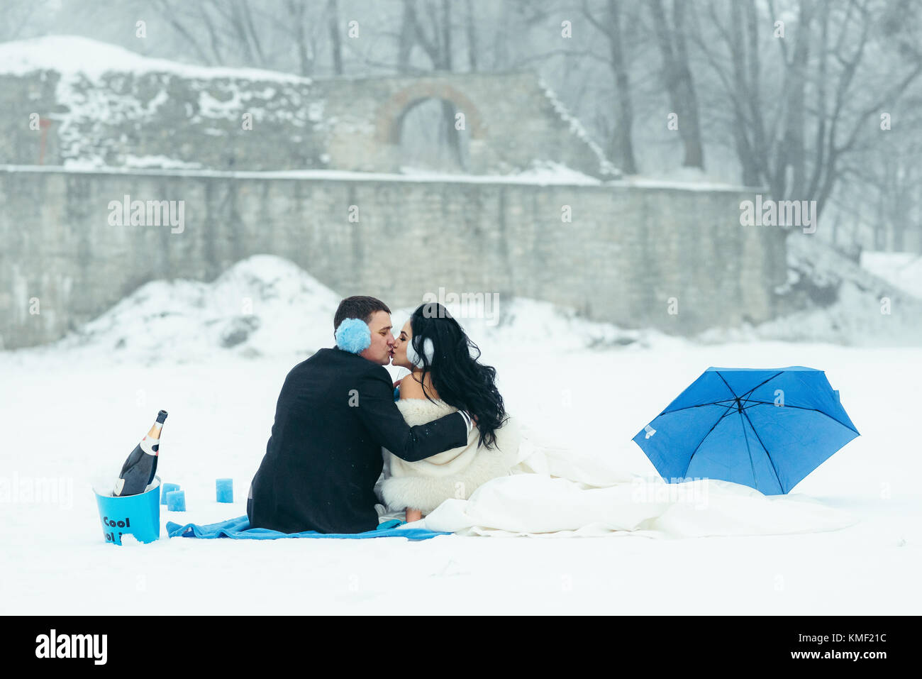 Back view of the newlyweds kissing while sitting on the plaid during their winter picnic in blue colours. Horizontal - Stock Image