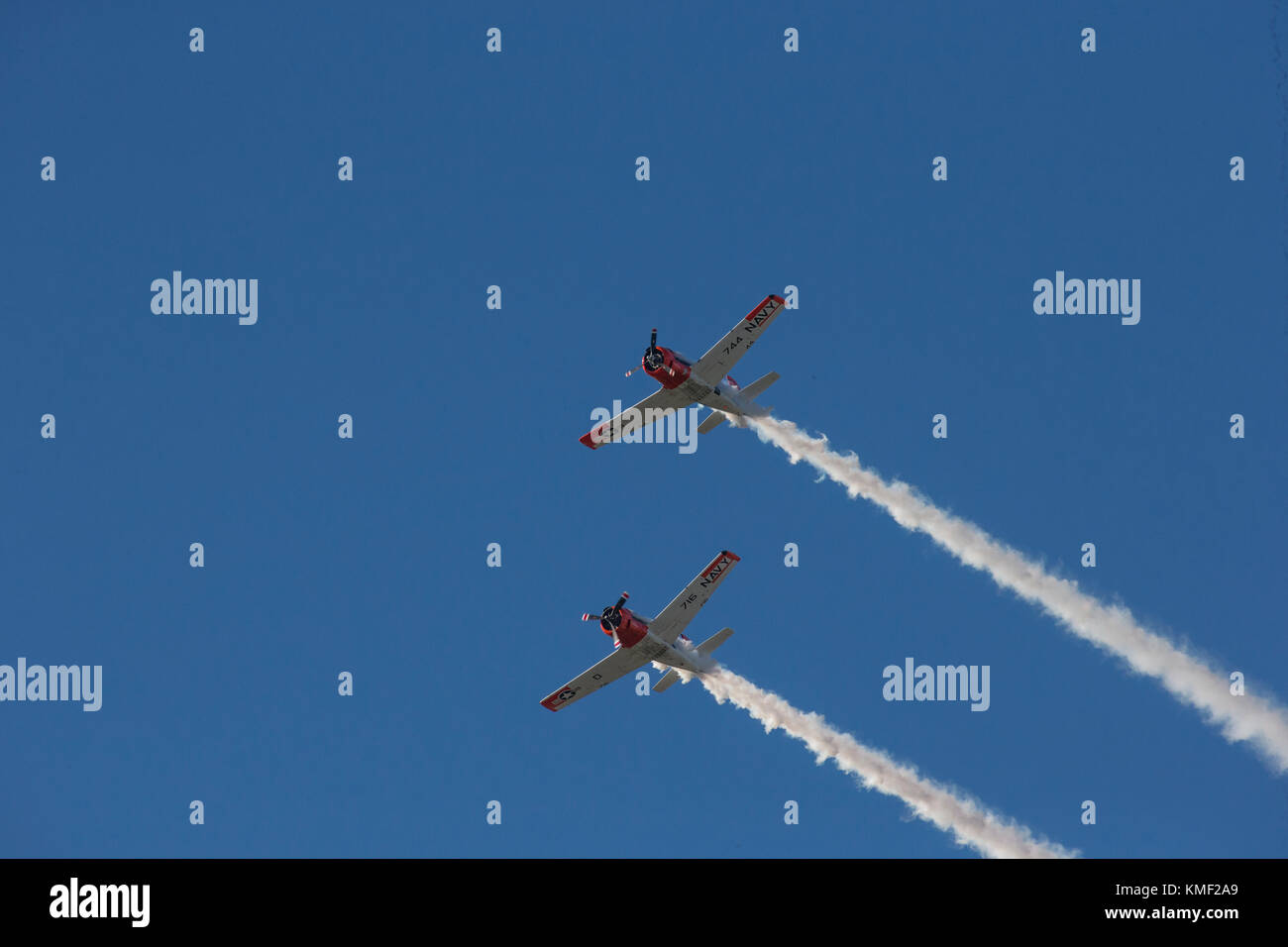 Two propeller airplanes flying together with smoke trail in deep blue sky - Stock Image