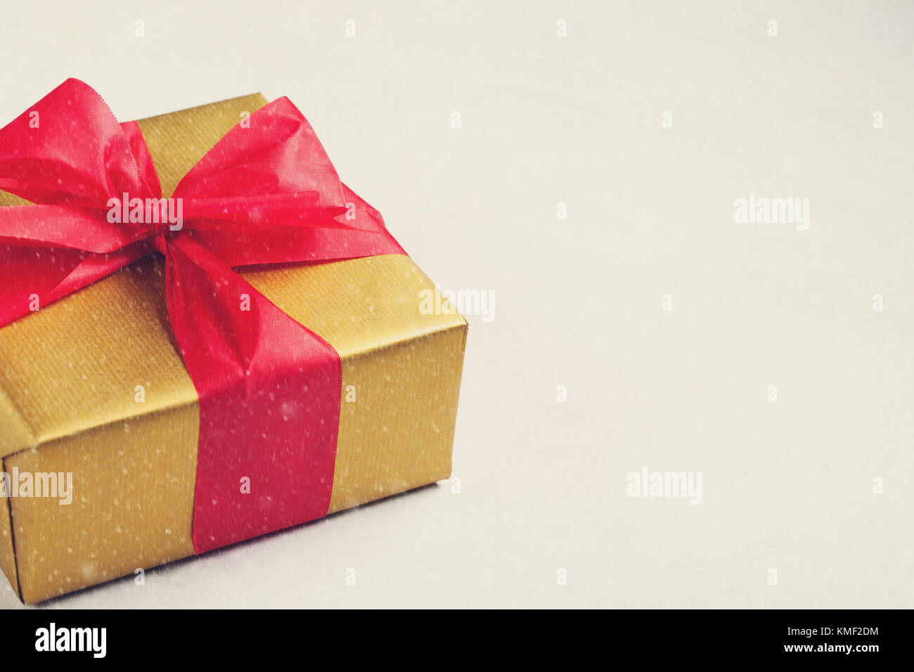 Golden gift box tied with a red ribbon isolated on white background. Copy space. vintage tones. - Stock Image