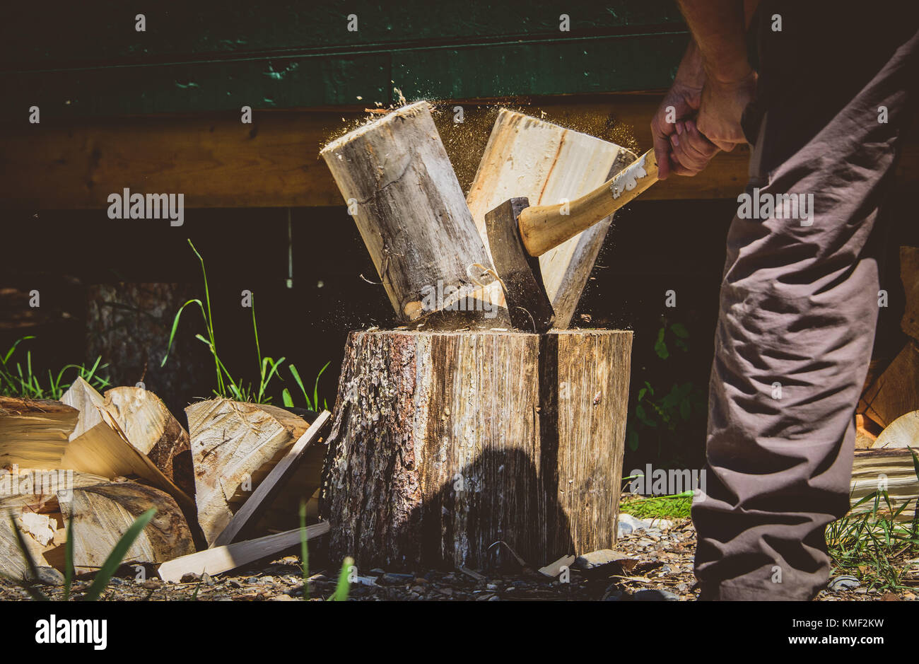 Splitting wood with an axe outdoors in the summer - Stock Image