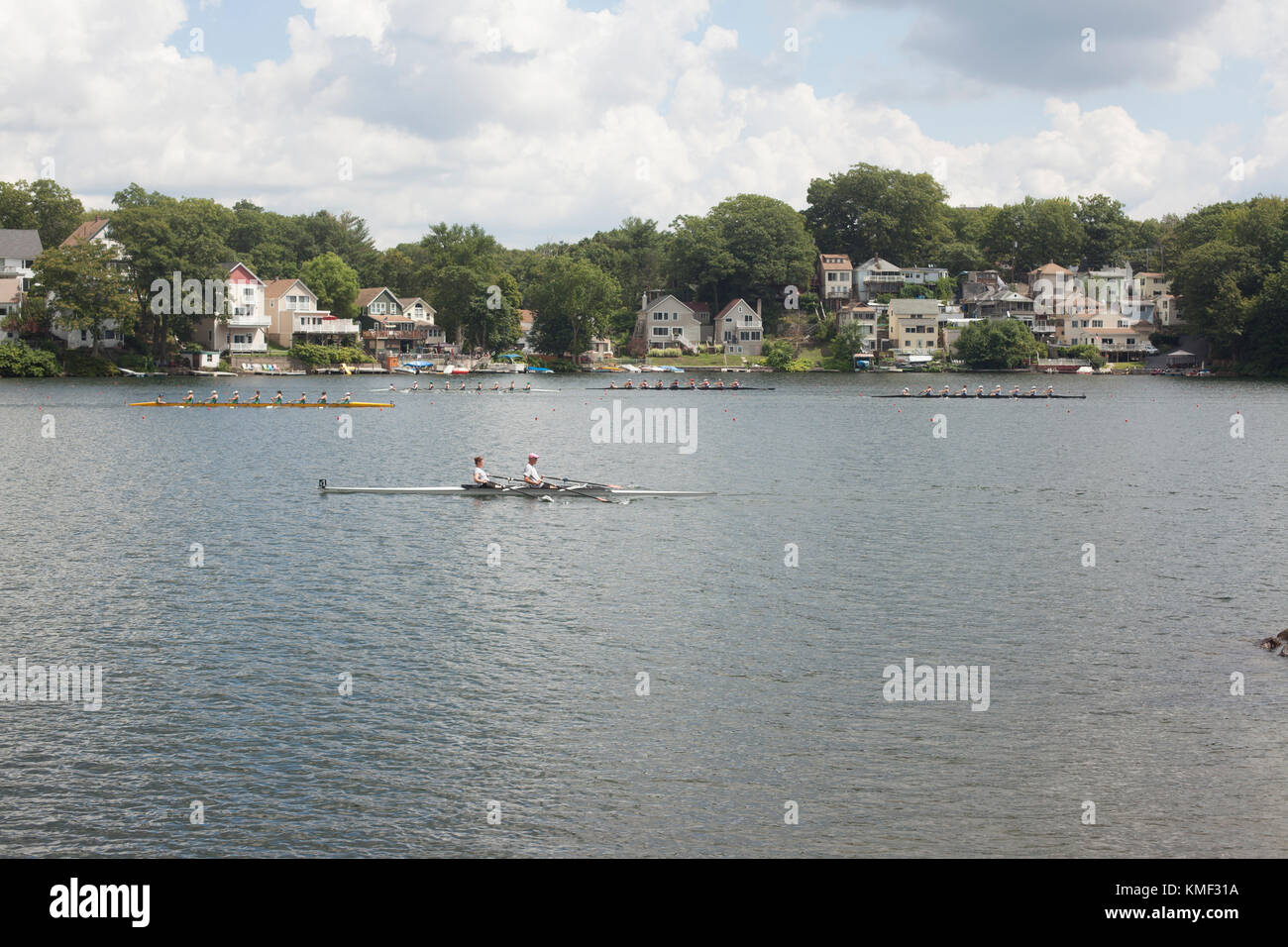 Crew boats racing in regatta on river with houses and trees on riverbank,Worcester,Massachusetts,USA - Stock Image