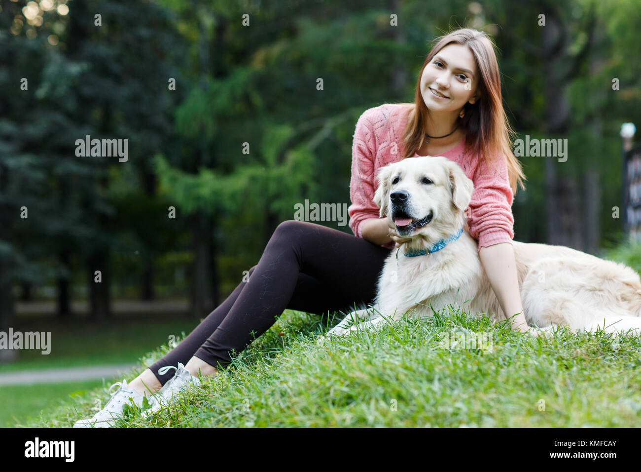 Photo of woman and dog sitting on lawn - Stock Image