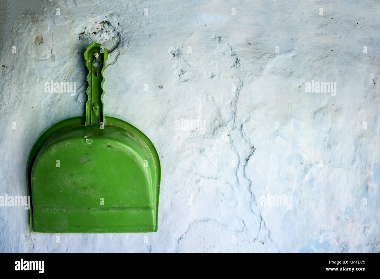 Green colored Dustpan hanging on the wall.Concept of cleanliness and neatness. - Stock Image