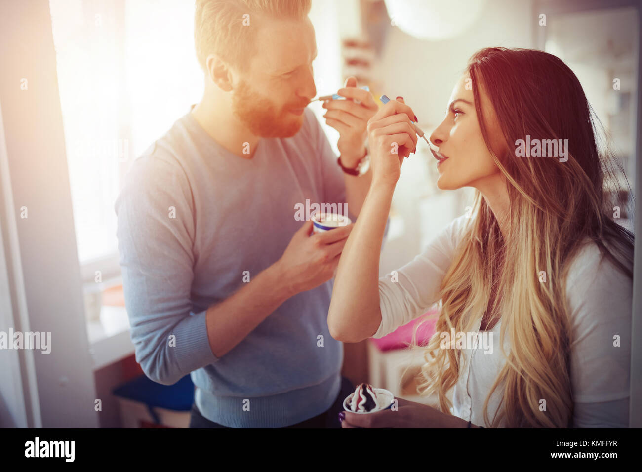 Couple having fun and laughing at home while eating ice cream Stock Photo