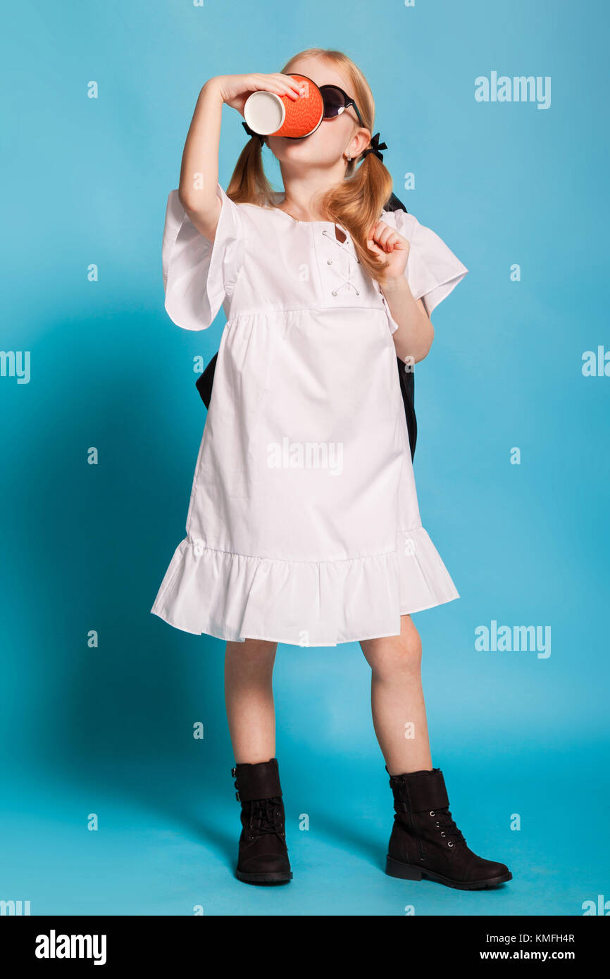 a little girl in the white dress and black shoes Stock Photo
