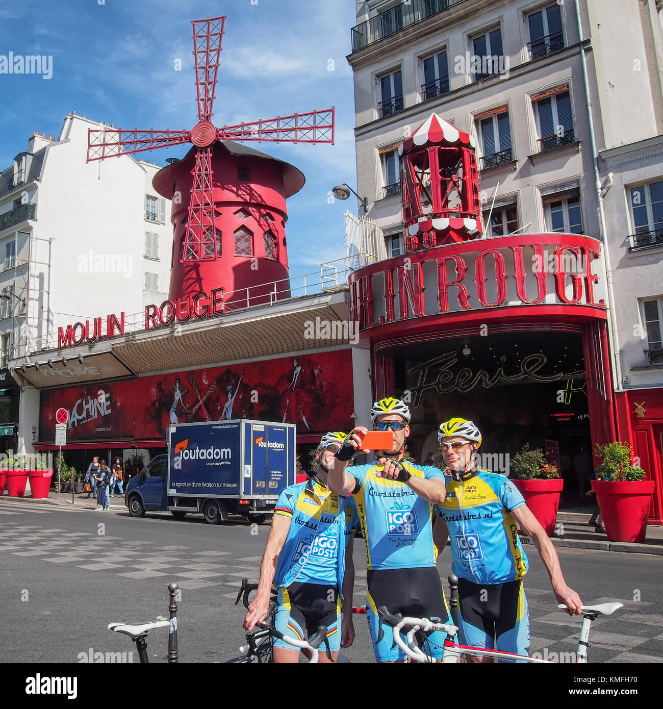 PARIS, FRANCE-MAY 6, 2016: Cyclists in the sport uniform do selfie in front of the Moulin Rouge. Moulin Rouge is - Stock Image