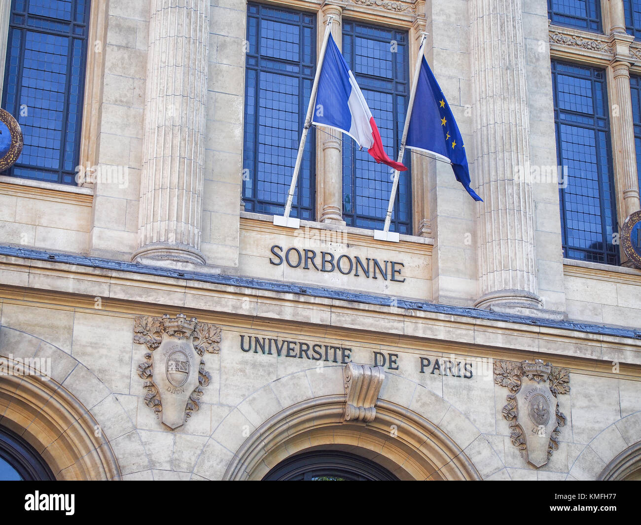 Title on the facade of the Sorbonne University bellow french and EU flags. - Stock Image