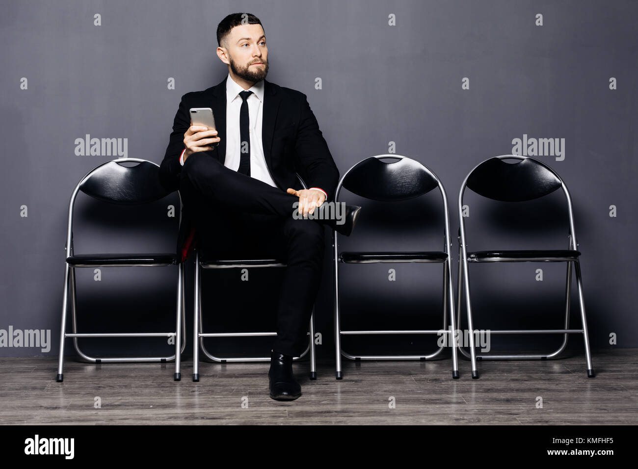 Ready for interview. Thoughtful man in formalwear holding phone and use it while sitting at the chair in waiting - Stock Image