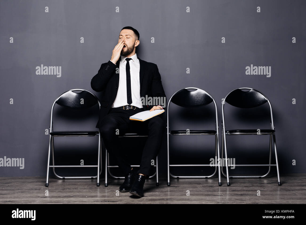 Serious bearded young man in glasses and formal wear is yawing sitting in the hall on chair Stock Photo