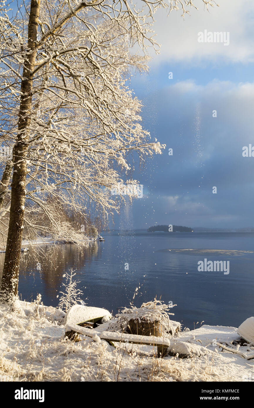 Beautiful view of Lake Pyhäjärvi, snowy ground, few rowboats and trees and snow falling from trees on - Stock Image