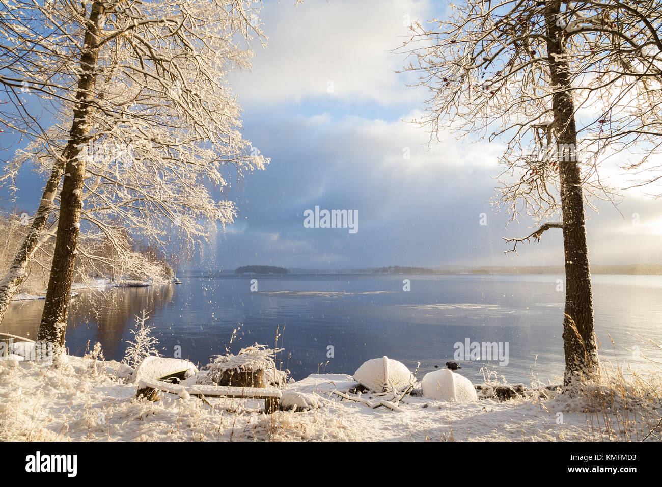 Beautiful view of Lake Pyhäjärvi, snowy ground, rowboats and trees and snow falling from trees on a sunny - Stock Image