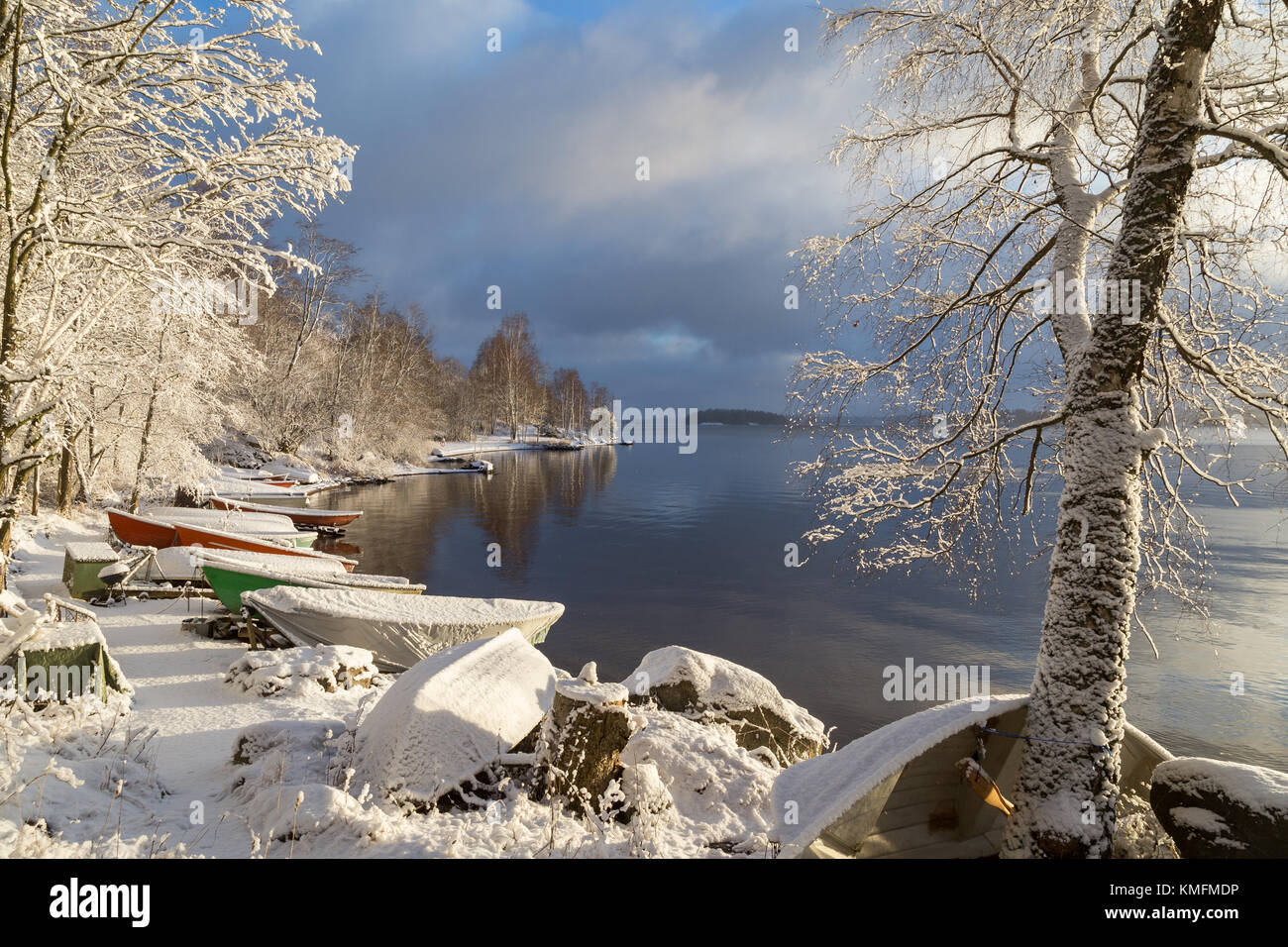 Beautiful view of Lake Pyhäjärvi, snowy ground, many rowboats and trees on a sunny day in the winter in - Stock Image