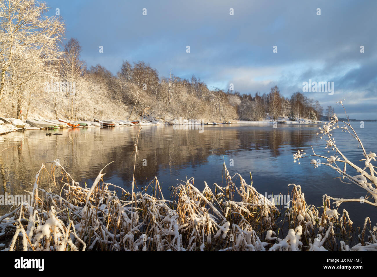 Beautiful view of snowy plants, trees, several rowboats and Lake Pyhäjärvi on a sunny day in the winter - Stock Image