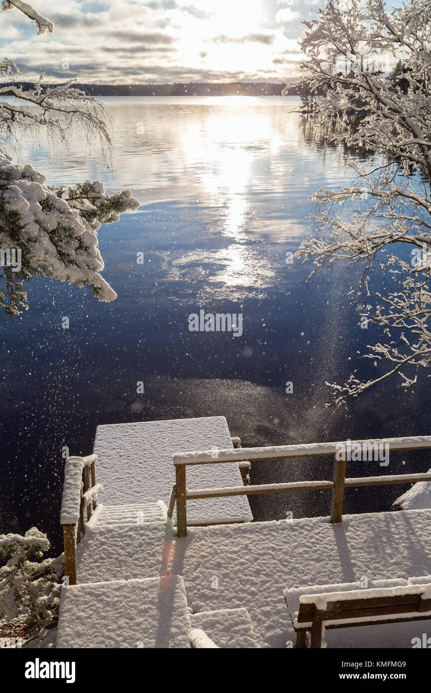 Beautiful view of Lake Pyhäjärvi, snowy trees and pier and snow falling from trees on a sunny day in the - Stock Image