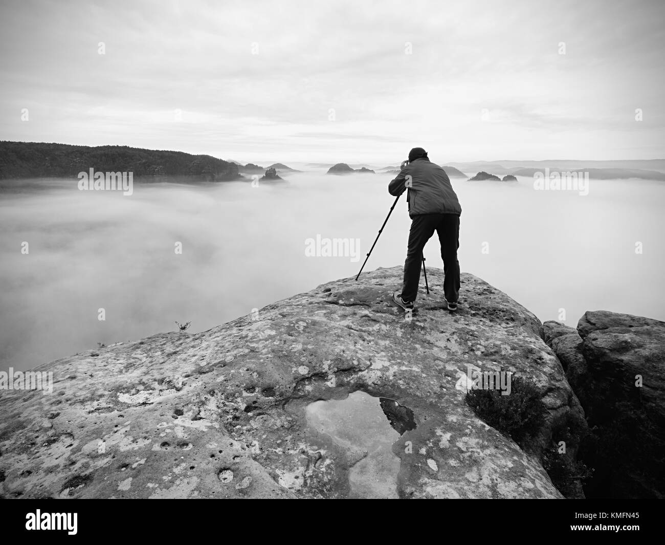 Photo artist in work. Photographer in rocky mountains. Traveller takes photos of dreamy majestic landscape, sunset - Stock Image
