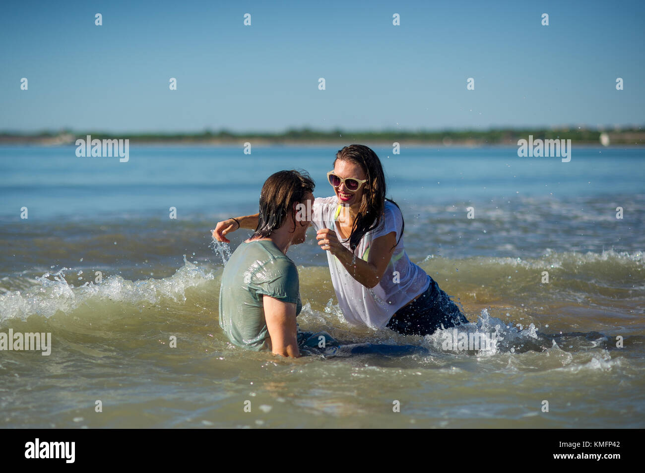 Young couple bathing in the sea. Guy and girl are merrily floundering in the water. - Stock Image